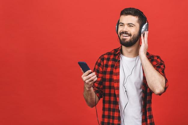 Изображение небритого человека 30 петь во время прослушивания музыки с наушниками и мобильным телефоном, изолированных на красную стену.