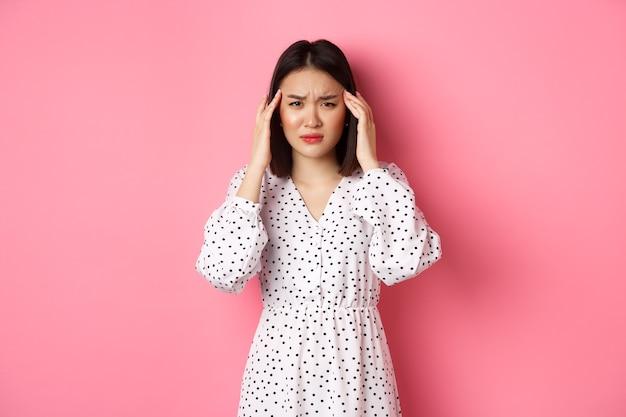 ピンクの背景の上に立って、頭痛、気分が悪いまたはめまい、目を閉じて頭をマッサージし、片頭痛に苦しんでいる動揺したアジアの女性の画像。
