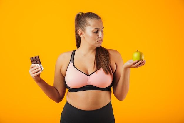 Изображение расстроенной полной женщины в спортивном костюме, держащей в обеих руках плитку шоколада и яблоко, изолированную на желтом фоне