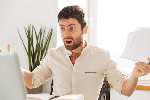 Изображение встревоженного офисного работника 30-х годов в белой рубашке, использующего ноутбук и бумажные документы на современном рабочем месте