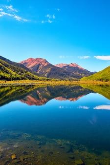 Изображение вертикального пейзажа озера в горах с осенними осинами и красными песчаными горными вершинами на фоне голубого неба