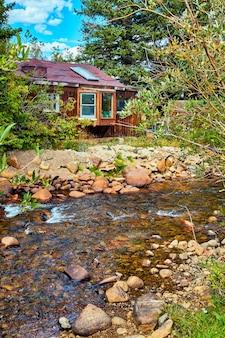 趣のある木造の小屋の隣にある垂直の川の入り江の詳細の画像