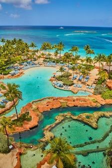 Изображение вида с балкона курортного отеля на бассейн со скатами, бассейн, пальмы и океан