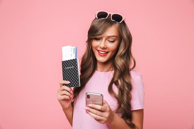 Изображение девушки-путешественницы 20-х годов с красивыми коричневыми замками, использующей смартфон, с паспортом и авиабилетами, изолированное на розовом фоне
