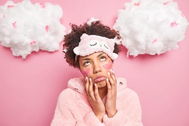朝の日課にうんざりしている女性の画像は、ピンクの壁に隔離されたパジャマに身を包んだ上向きの退屈な第3の表情で頬に手を保ちます