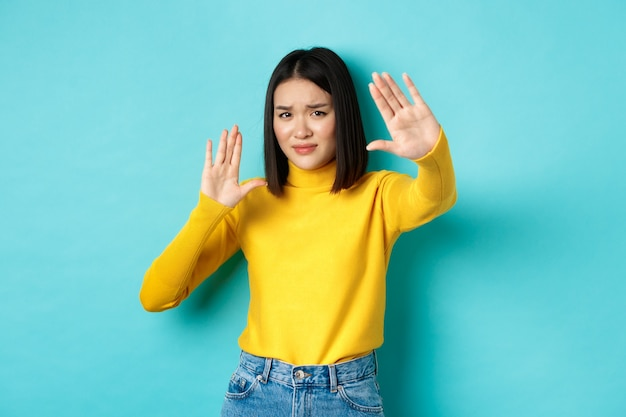 Изображение женщины, которая чувствует себя неуютно перед камерой, закрывает лицо руками и хмурится, умоляет остановиться, стоит на синем фоне.