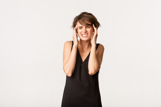 ひどい頭痛があり、頭に触れ、痛みを伴う片頭痛から顔をゆがめ、白の上に立っている女性の画像。