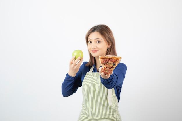 사과나 피자를 무엇을 먹을지 선택하려고 앞치마를 입은 여성의 이미지