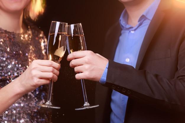 鮮やかなドレスを着た女性と黒の背景にシャンパンとワイングラスを持つ男性の画像