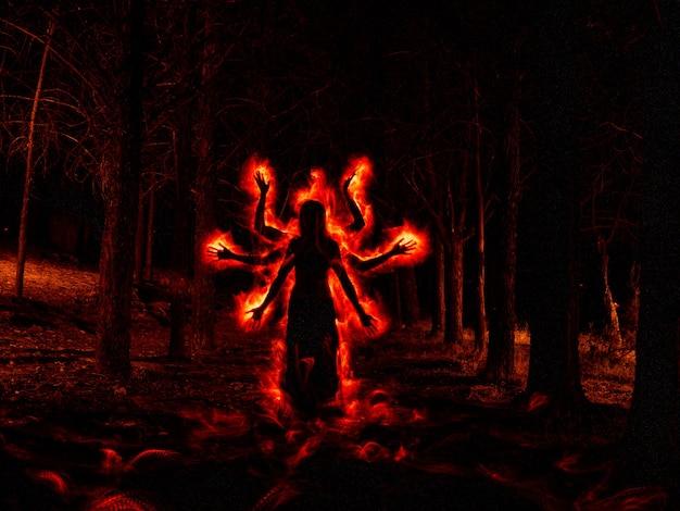 Изображение женщины в темном лесу с эффектом красного огня по бокам