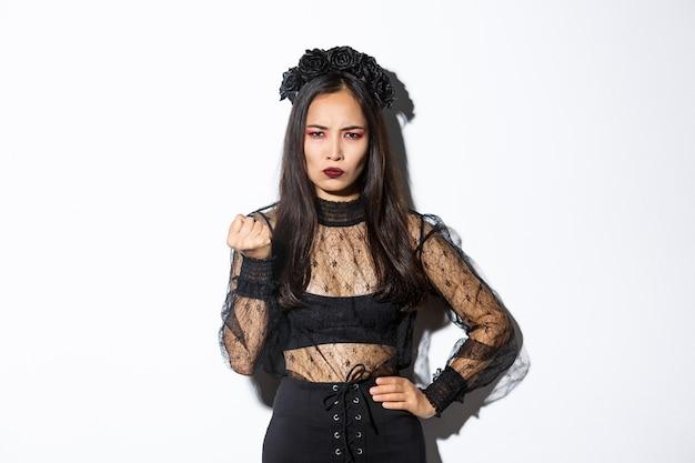 ハロウィーンの邪悪な魔女の衣装を着て、拳で誰かを脅かす女性の画像