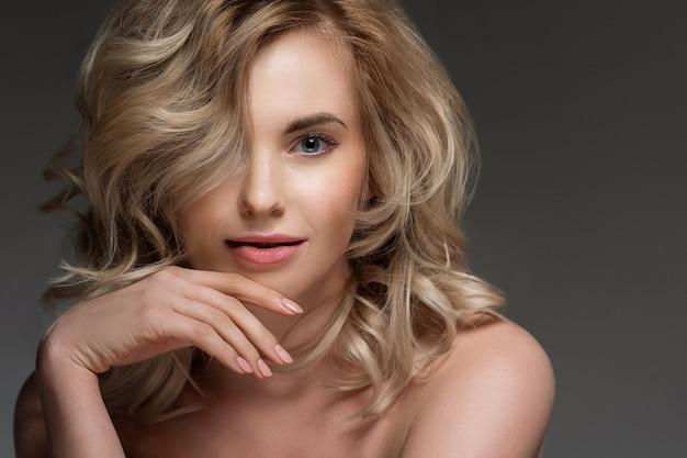 裸の肩を持つ巻き毛の女性の画像