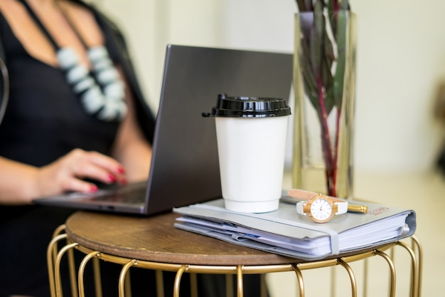 흰색 테이블에 카푸치노 커피와 함께 커피숍에서 컴퓨터 노트북 작업을 하는 여성의 이미지. . 고품질 사진