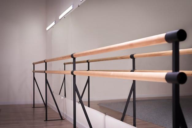 댄스 스튜디오에 있는 나무 막대의 이미지입니다. 춤, 발레의 개념입니다. 전문 장비. 혼합 매체