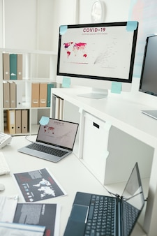 Изображение рабочего места с монитора компьютера и портативных компьютеров и документов со статистикой covid-19 в больнице