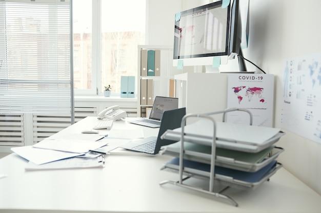 Изображение рабочего места с монитором компьютера на нем и документы в кабинете врача