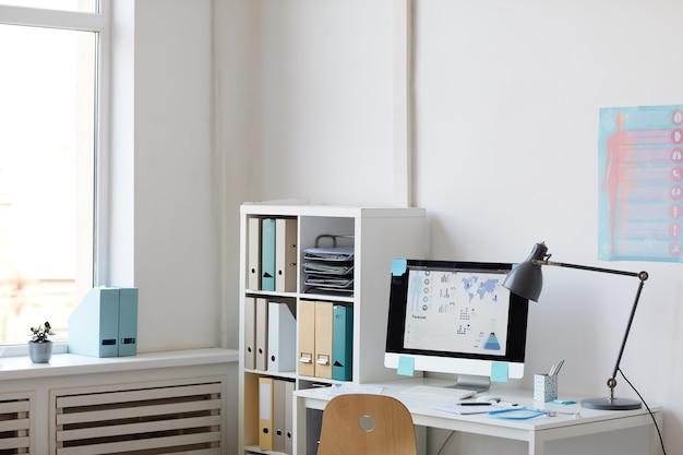 Изображение рабочего места с компьютером на столе в офисе современного врача