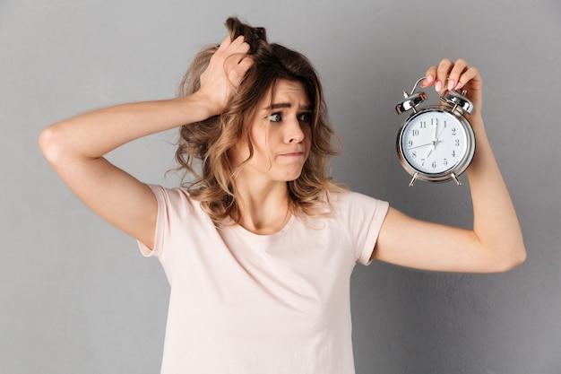 T- 셔츠 들고 머리와 알람 시계 회색에 걱정 된 여자의 이미지