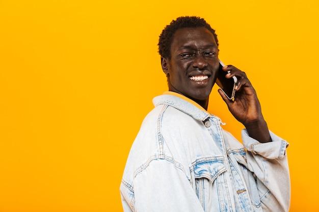 笑顔と携帯電話で話しているデニムジャケットの若いアフリカ系アメリカ人の男の画像