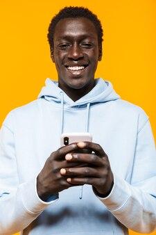 携帯電話を笑顔で保持しているストリートウェアパーカーの若いアフリカ系アメリカ人の男の画像