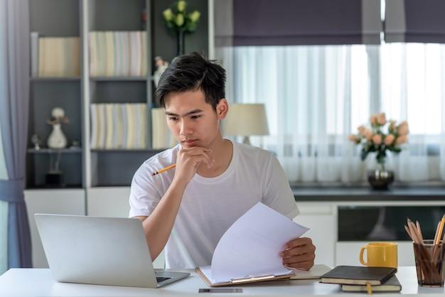 自宅でラップトップを使用して仕事を分析する若いアジア人ビジネスマンの画像。
