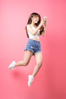 ピンクにジャンプする若いアジアの女の子の画像