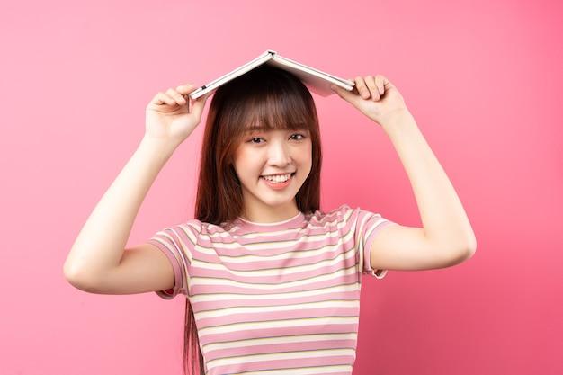 Изображение молодой азиатской девушки в розовой футболке на розовом