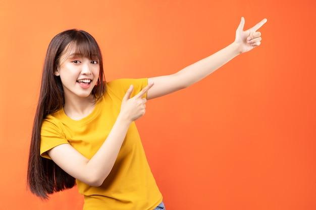 Изображение молодой азиатской женщины в желтой футболке на оранжевом