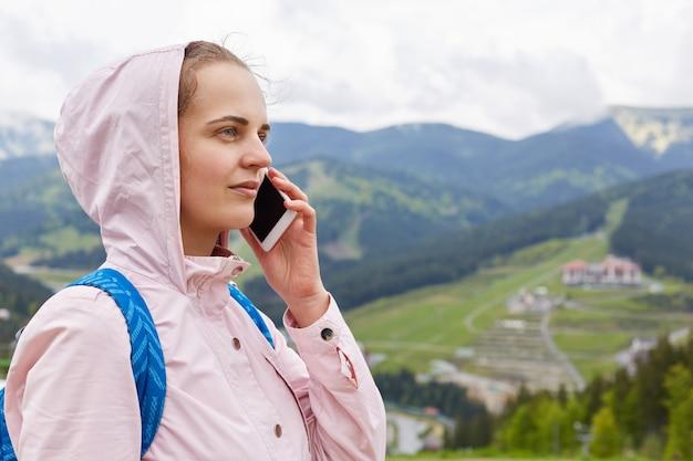 スマートフォンを耳の近くに持ち、電話で話し、自分の前を見て、山の周りでポーズをとり、フード、ジャケット、青いバックパッカーを身に着けて、景色を楽しみながら若い魅力的な探検家の画像。