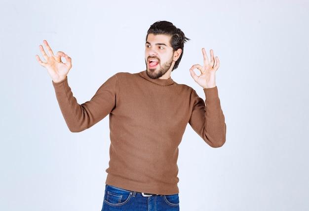大丈夫なジェスチャーを示す茶色のセーターを着た若い魅力的な男性の画像。高品質の写真