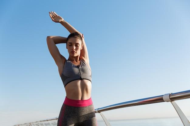 海辺の遊歩道でトレーニングを実行する前に体を伸ばす若い魅力的な女性の画像