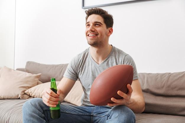 Изображение молодого холостяка, улыбающегося, отдыхая дома и смотрящего на американский футбол с пивом и мячом в руках