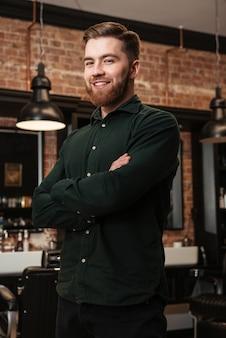 Изображение молодого бородатого мужчины, стоящего в парикмахерской