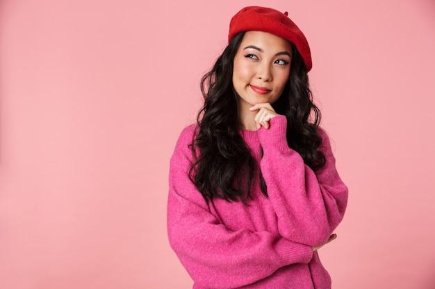 考えたり夢を見たりするベレー帽を身に着けている長い黒髪の若い美しいアジアの女の子の画像