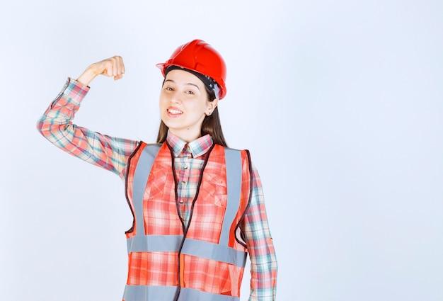 幸せな表情で立っているヘルメットの若い美しい女性エンジニアの画像。