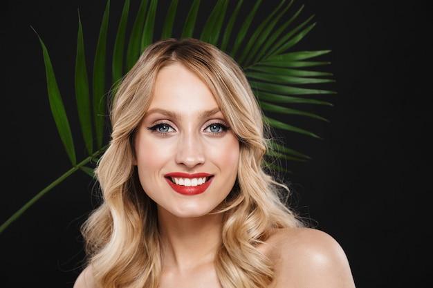 Изображение молодой красивой женщины с ярким макияжем красными губами позирует изолированным с зеленым цветком листьев.