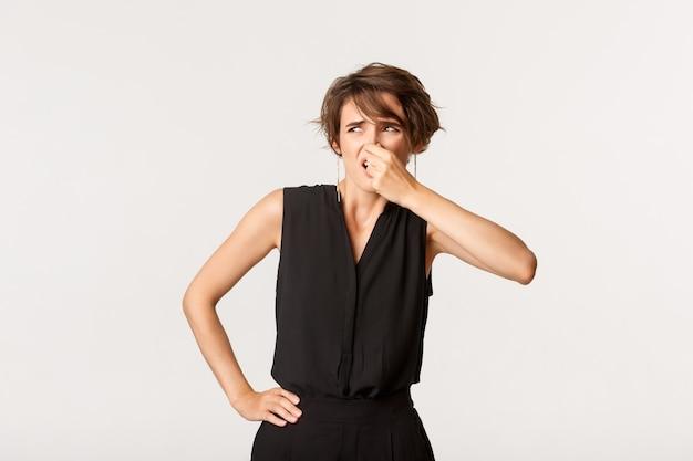Изображение молодой обеспокоенной женщины, жалующейся на отвратительный запах, зажатой носом и смотрящей влево, стоя белой.