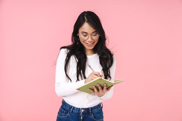 Изображение молодой брюнетки азиатской женщины в очках, делающей заметки в дневнике, изолированном на розовом