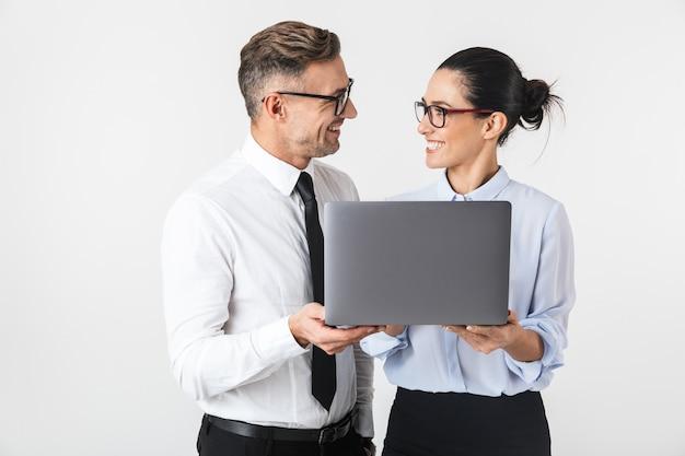 Изображение пары молодых коллег по бизнесу, изолированных на белой стене с помощью портативного компьютера.