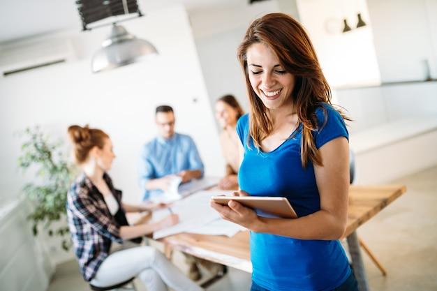 タブレットを見ている若いビジネス女性の画像