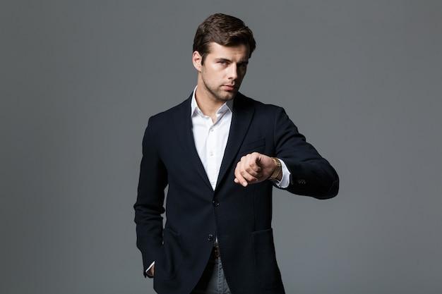 灰色の壁に隔離された腕時計を見て黒いジャケットを着た30代の青年実業家の画像