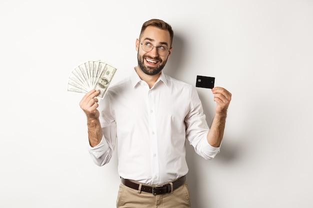 クレジットカードとお金を持って、左上隅を見て、白い背景の上に立って買い物を考えている青年実業家の画像。