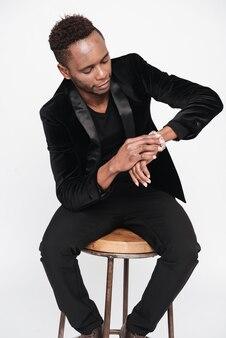Изображение молодого бизнесмена позирует в студии, глядя на часы. изолированные на белом фоне.
