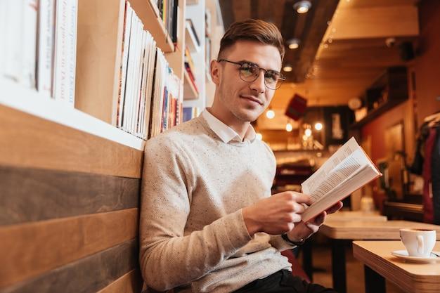 Изображение молодого веселого человека, сидящего в кафе, читая книгу и смотрящую на камеру.