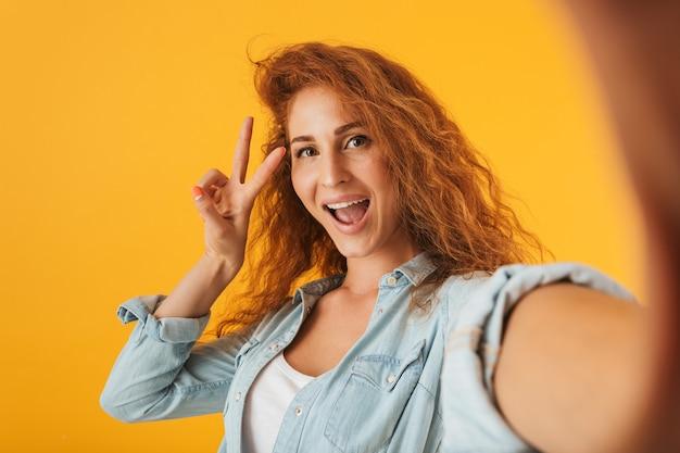 Изображение молодой веселой женщины, улыбающейся и показывающей знак мира при съемке селфи, изолированной на желтом фоне