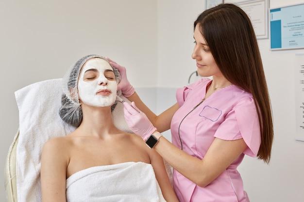 Изображение молодой женщины с маской пилинга стороны, косметикой курорта. женщина получая уход за лицом косметологом в салоне курорта. косметолог наносит косметическое средство специальной кистью. концепция ухода за кожей.