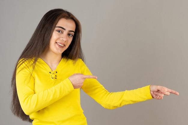 Изображение молодой девушки в желтой верхней стоящей и позирующей на серой стене.
