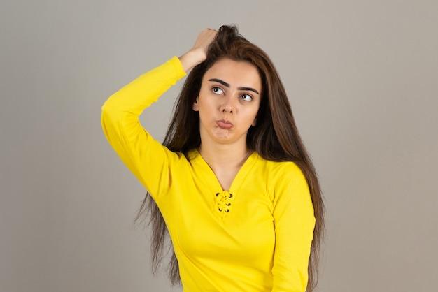 黄色のトップに立って灰色の壁にポーズをとっている少女の画像。