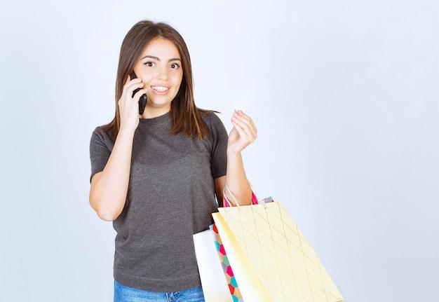 電話で話し、買い物袋を持っている少女の画像。
