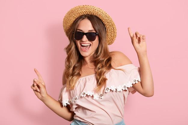 Образ молодой девушки с довольным выражением лица танцует на розовой стене, слушает любимые песни, женскую модель в модной блузке, шляпу и солнцезащитные очки, веселится на пляже с друзьями.